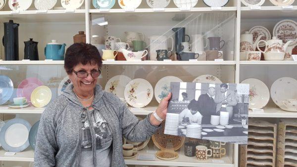 Freda Crawford (nee Desai) at Te Toi Uku holding an image of herself working at Crown Lynn in 1958